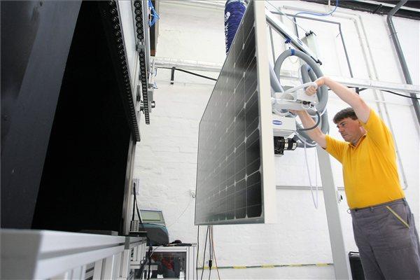 A cég egyik dolgozója egy frissen elkészült napelem ellenőrzését végzi az Agulhas-Solar Ipari, Kereskedelmi és Szolgáltató Kft. szolnoki napelemösszeszerelő üzemében, az AC-DC Logisztikai Parkban, a néhány éve megszűnt Mondi Papírgyár területén. MTI Fotó: Bugány János