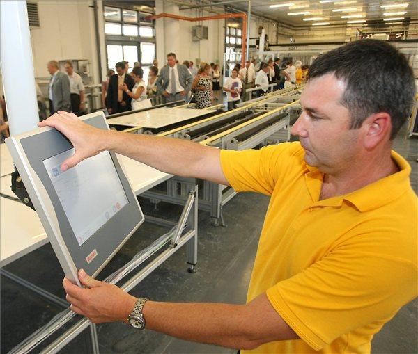 A cég egyik dolgozója irányítja a napelem összeszerelés munkafolyamatát a gyártósor vezérlőberendezését. MTI Fotó: Bugány János